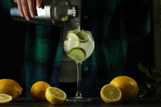 Woman making a cocktail with citrus against dark background
