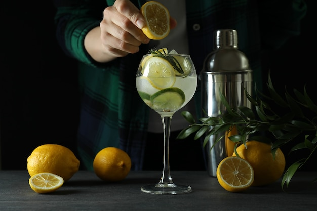Woman making a cocktail with citrus against dark surface