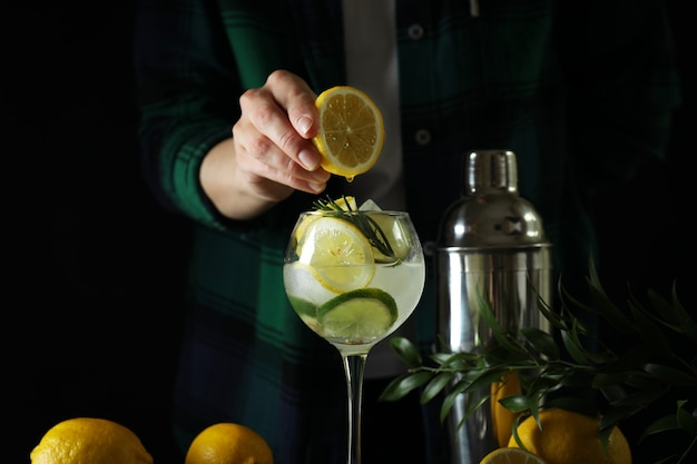 Woman making a cocktail with citrus against dark