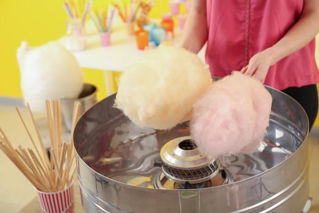Женщина делает сладкую вату на ярмарке