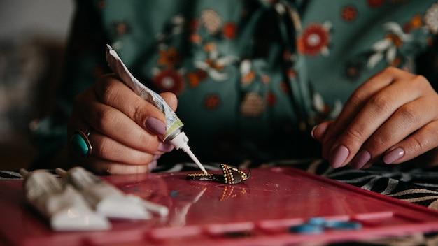 接着剤を使って工芸品を作る女性
