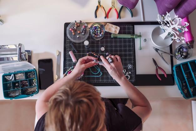 Женщина делает изделия из полимерной глины и серебра в мастерской.
