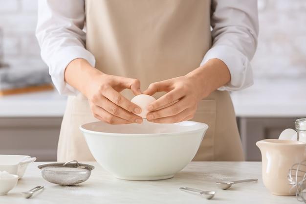 Женщина делает тесто на столе на кухне