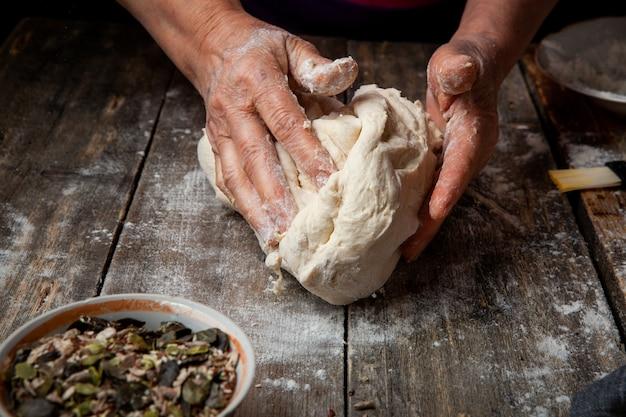 Женщина, делая тесто на деревянный стол крупным планом.