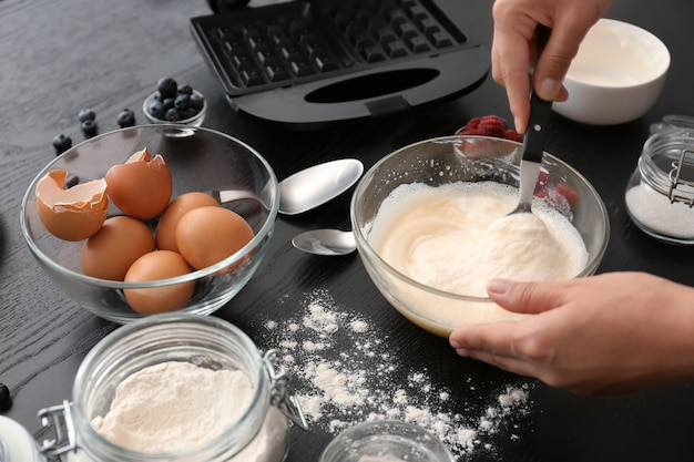 Woman making dough for waffles in kitchen