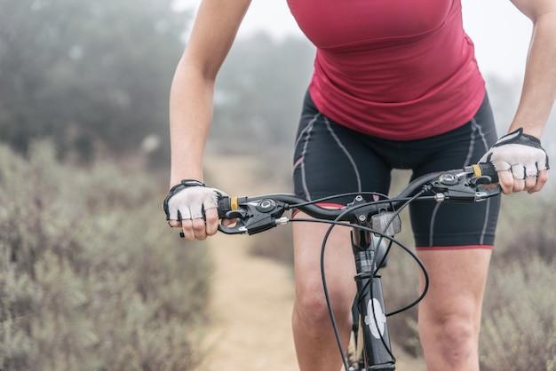 マウンテンバイクで下り坂を作る女性。人とスポーツについての概念