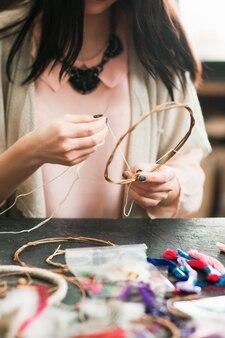 アートスタジオでドリームキャッチャーを作る女性