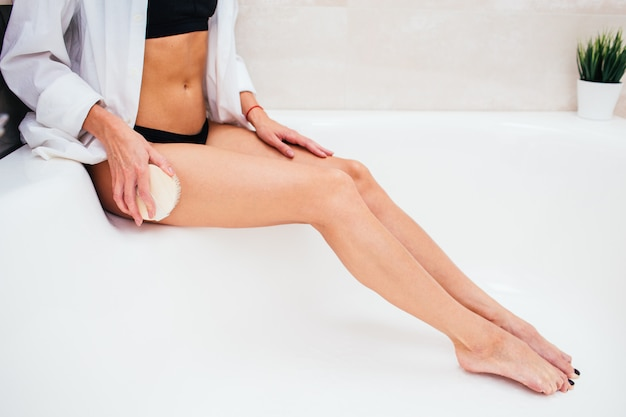 Woman making dry massage with natural brush. girl in black underwear making skin peeling in the bathroom. anti-cellulite, exfoliation, home skincare concept. face is not visible.
