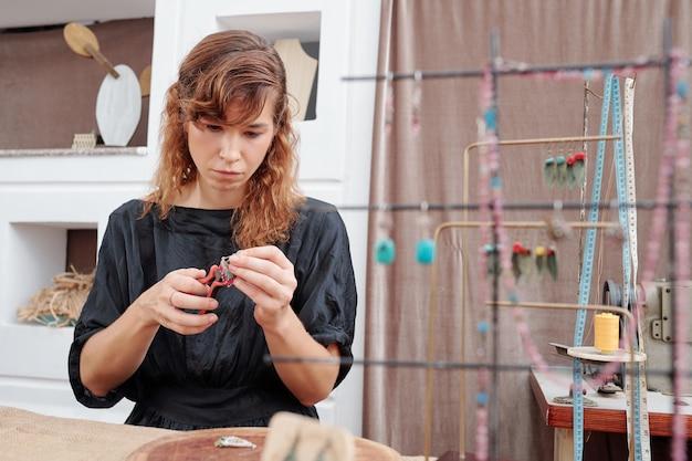 Женщина делает серьги в своей студии
