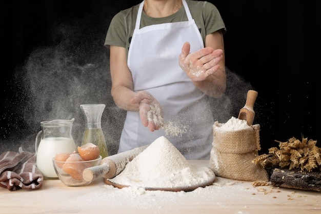Woman making easter baking at home bakery. woman preparing bread dough on a wooden table in a bakery nearby