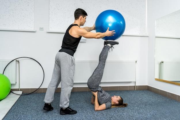 Женщина делает упражнения с фитболом с личным тренером в фитнес-зале