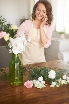 Donna che fa la disposizione floreale e la chiamata