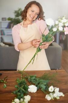 Donna che fa la disposizione floreale e parla al telefono
