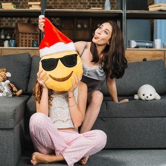 Woman making funny expression while holding santa claus smiley emoticon in front of her female friend's face