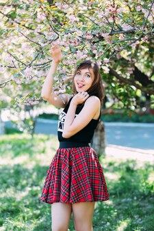 꽃이 만발한 봄 나무 근처 재미있는 얼굴을 만드는 여자. 벚꽃, 피 벚꽃 나무 근처 여자