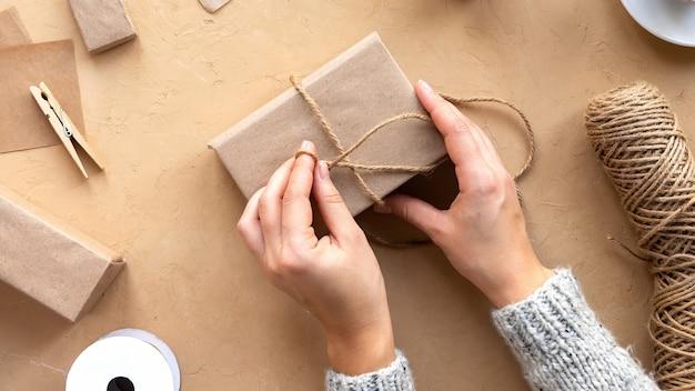 Donna che fa una confezione regalo, cose fatte a mano e composizione di materiali. vista dall'alto