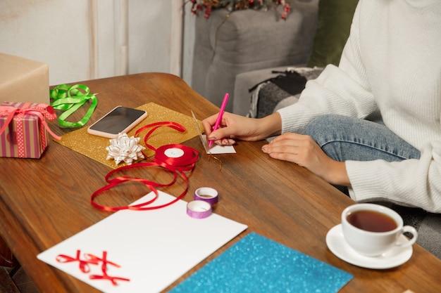 Женщина делает поздравительную открытку на новый год и рождество 2021 года для друзей или семьи, бронирование лома, diy. пишет письмо с наилучшими пожеланиями, используя инструменты для создания своей самодельной открытки. праздники, торжество