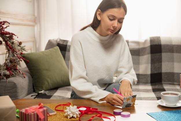 友人や家族のスクラップのために2021年の新年とクリスマスのグリーティングカードを作る女性