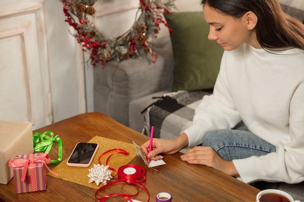 友人や家族のための新年とクリスマス2021年のグリーティングカードを作る女性