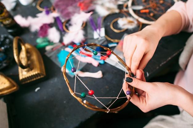Woman making handmade dreamcatcher with beads