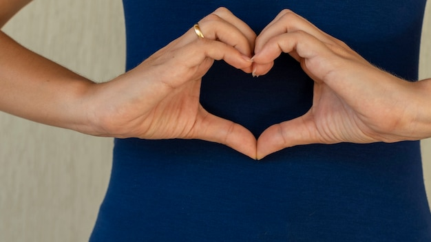 Женщина делает руки в форме сердца сердечное медицинское страхование пожертвование социальной ответственности