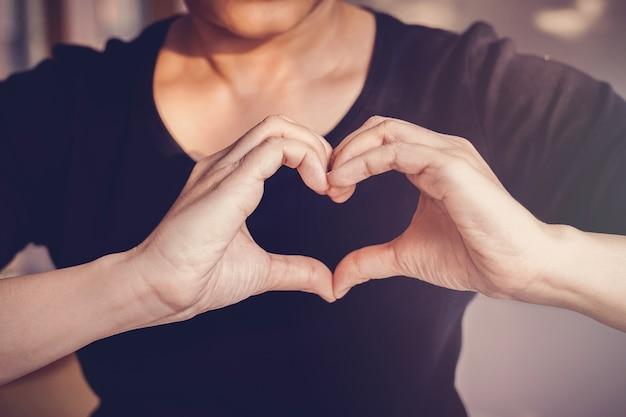 ハート形のサイン、健康保険、寄付ボランティアコンセプトで手を作る女性