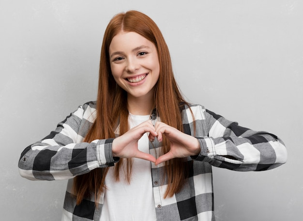 Woman making heart gesture front view