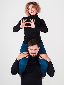 Woman making heart shape with hands on top of man
