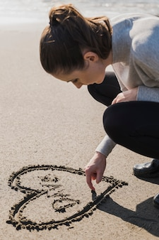 Woman making heart on wet sand