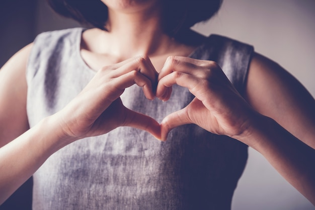 Woman making her hands in heart shape, heart health insurance