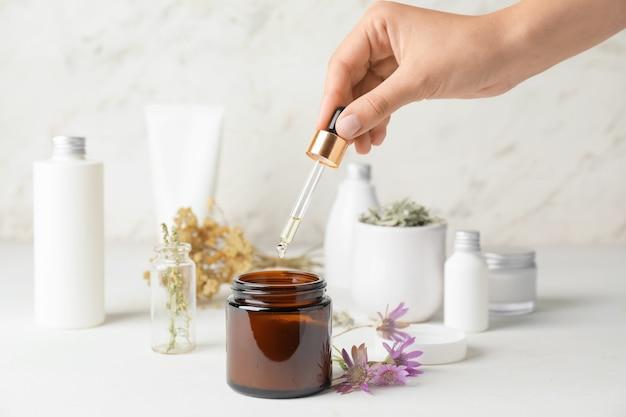 テーブルの上でハーブベースの薬を作る女性
