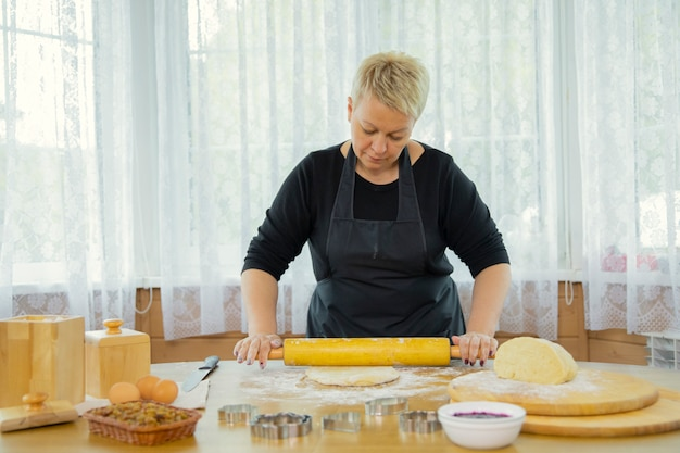 Woman making homemade cookies rolls dough with rolling pin for homemade baking