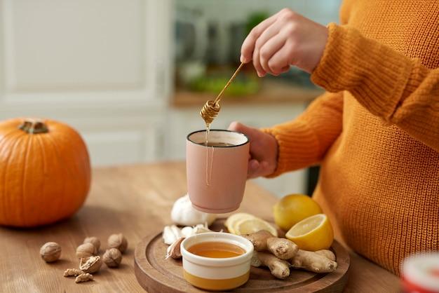 蜂蜜で熱いお茶を作る女性