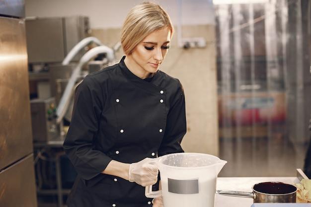 상업용 주방에서 아이스크림을 만드는 여자.