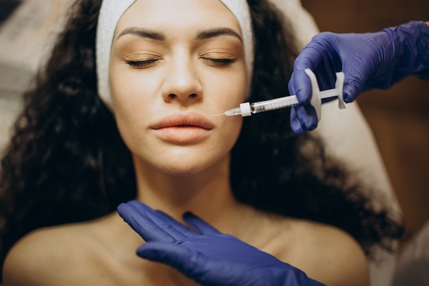 Woman making injections at cosmetologist