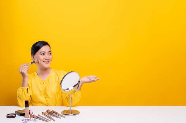 Woman making make-up near mirror and sitting at the desk