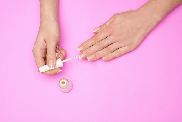 Женщина делает маникюр сама на розовой поверхности.