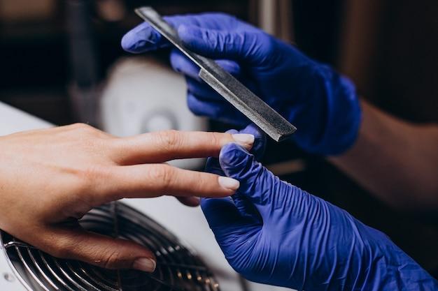 Женщина делает процедуру маникюра в салоне красоты
