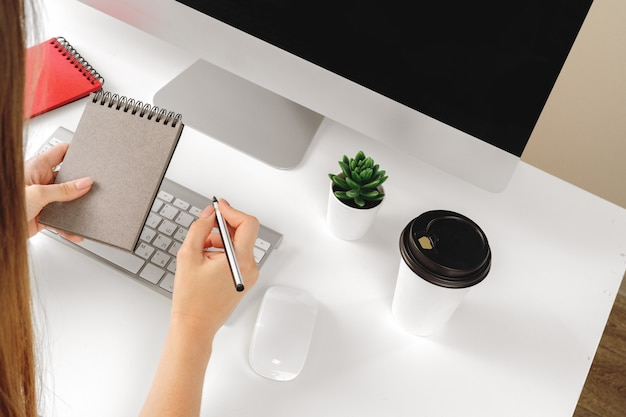 Woman making notes in notepad in an office