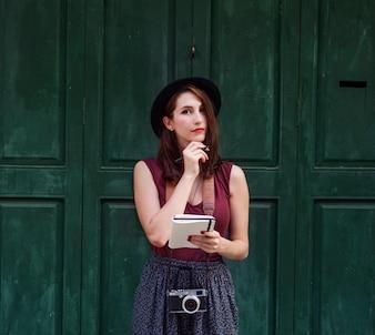 都市のコンセプトの外でノートを作る女性