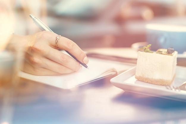 커피 숍에 앉아있는 동안 메모를 만드는 여자