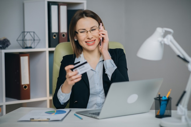 Woman making online purchase. online payment service. close up of woman hands hold credit card and using laptop for online shopping.