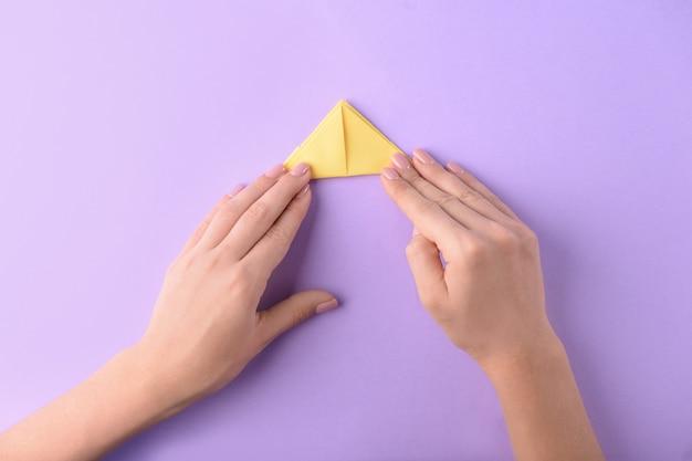色の背景に折り紙のボートを作る女性