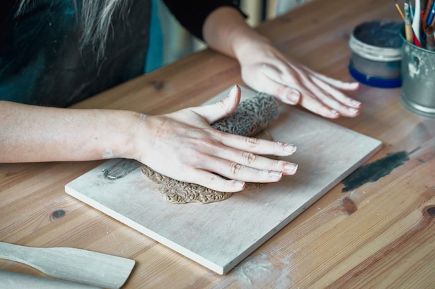 Woman making pattern on ceramic plate
