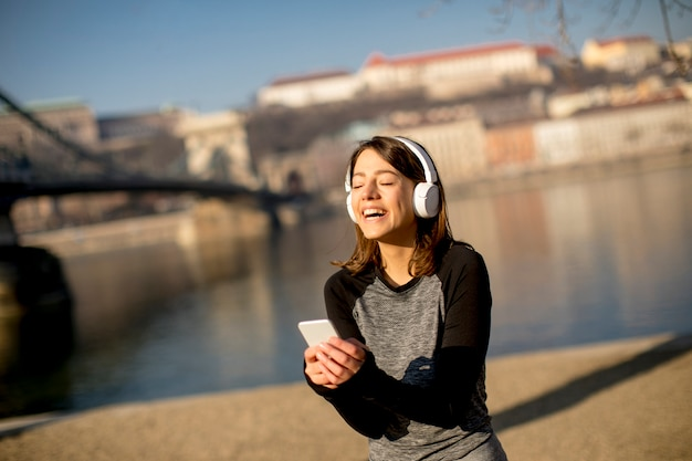 Woman making a pause after the exercise and using mobile phone