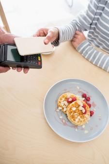 Женщина делает платеж через nfc