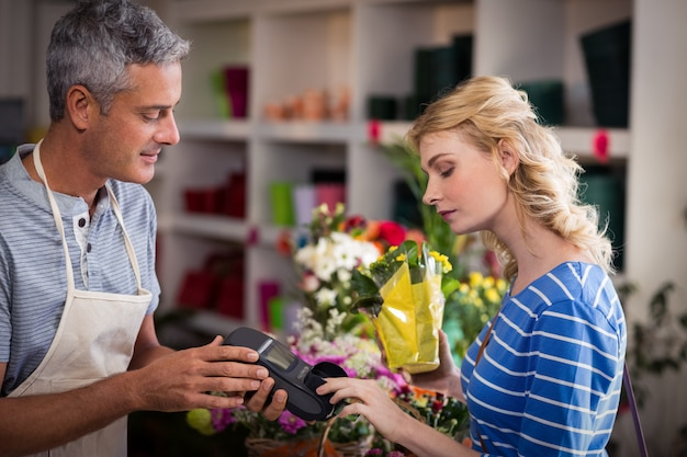 Woman making payment with her credit card to florist