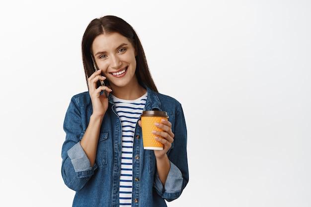 電話をかけ、持ち帰り用のコーヒーを飲む女性。社会人。スマートフォンを使用して笑顔の女性と白いカフェから黄色いカップを保持します。