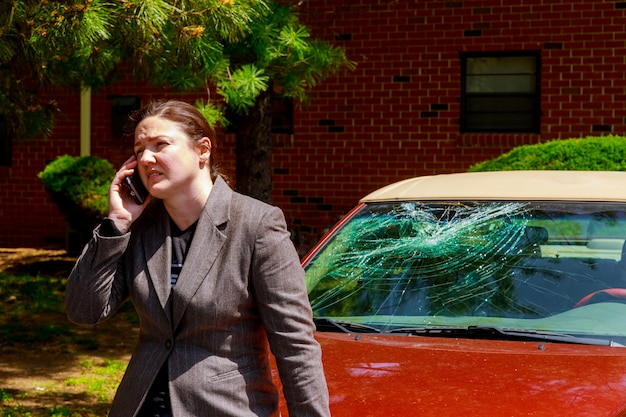 Woman making a phone call by the damaged windshield after a car accident