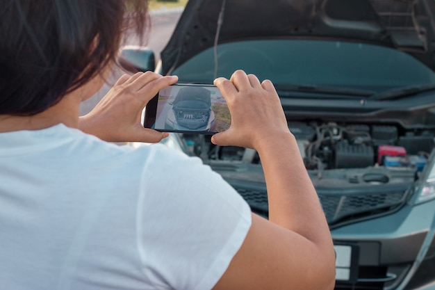 Woman making photo to the engine of a car